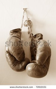 stock-photo-hang-up-the-gloves-old-worn-leather-boxing-gloves-in-sepia-tones-hanged-up-on-grunge-style-wall-72810151